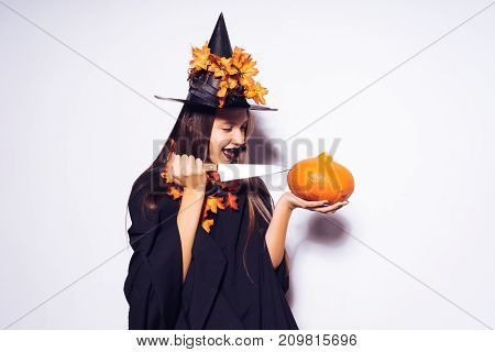 a girl in a halloween costume is going to cut a small pumpkin