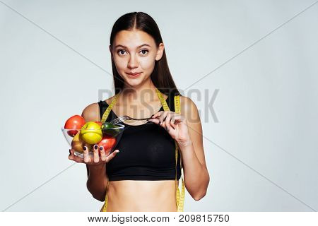 the girl joyfully looks forward holding a bowl of vegetables and an apple in hands
