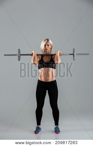 Full length portrait of a motivated muscular adult sportswoman standing and lifting a barbell isolated over gray background