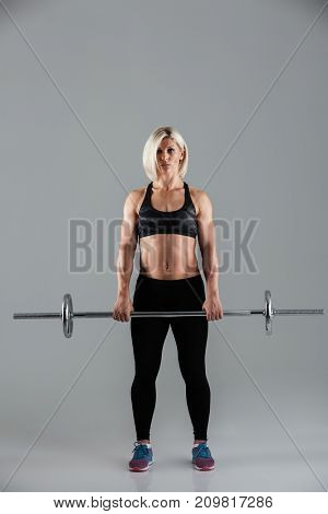 Full length portrait of a confident muscular adult sportswoman standing with a barbell isolated over gray background