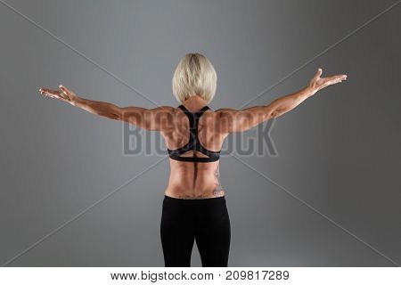 Back view portrait of a muscular adult sportswoman standing with hands outstretched isolated over gray background
