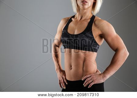 Cropped image of a muscular woman in sportswear standing with arms on hips isolated over gray background