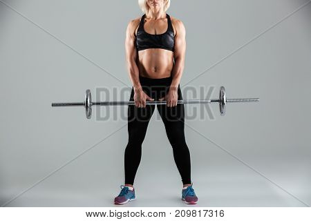 Cropped image of a muscular adult sportswoman standing and holding barbell isolated over gray background