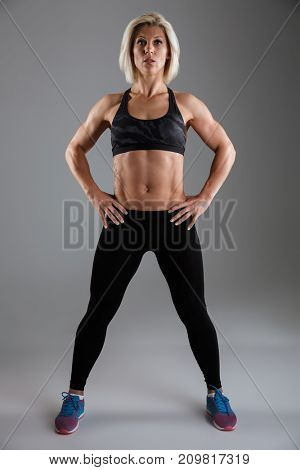 Full length portrait of a confident muscular adult sportswoman standing with arms on hips and looking at camera isolated over gray background
