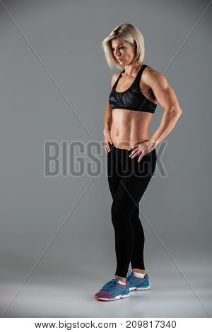 Full length portrait of an attractive muscular sportswoman standing with arms on hips isolated over gray background