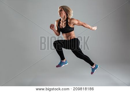 Full length portrait of a strong muscular adult woman jumping while running isolated over gray background