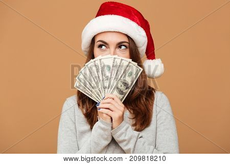Picture of caucasian lady wearing christmas hat standing isolated holding money. Looking aside.