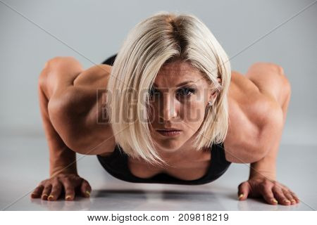 Close up portrait of a confident muscular adult sportswoman doing push-ups and looking at camera isolated over gray background