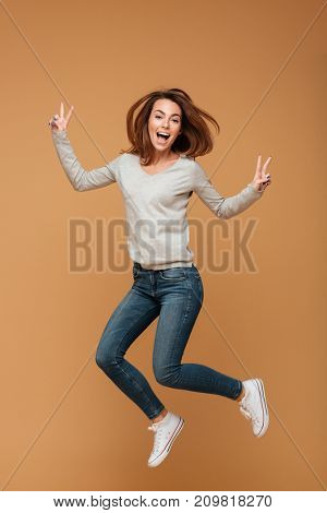 Photo of screaming happy caucasian woman jumping isolated make peace gesture. Looking camera.