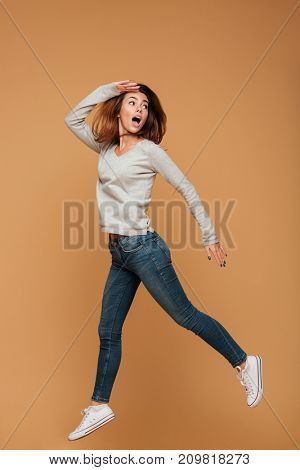Image of screaming caucasian woman jumping isolated. Looking aside.