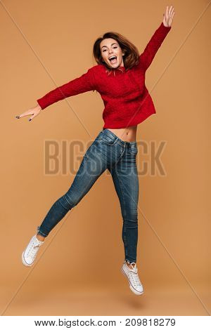 Image of smiling caucasian woman dressed in sweater jumping isolated. Looking camera.