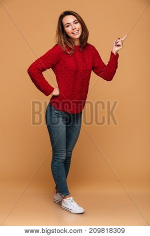 Picture of happy caucasian woman dressed in sweater standing isolated. Looking camera and pointing.