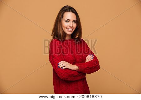 Young happy caucasian lady with arms crossed dressed in sweater standing isolated. Looking camera.