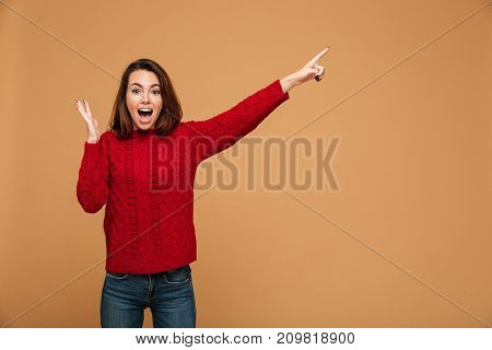 Image of shocked caucasian woman dressed in sweater standing isolated. Looking camera and pointing.