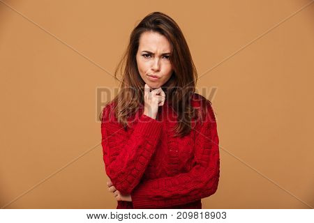 Image of confused caucasian woman dressed in sweater standing isolated. Looking camera.