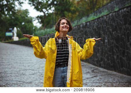 Portrait of a happy teenage girl wearing raincoat walking under the rain on a city street