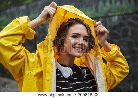 Portrait of a smiling joyful teenage girl with headphones wearing raincoat outdoors