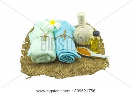 Spa herbal compressing ball white frangipani flowers (Plumeria spp flower Apocynaceae flower Pagoda tree flower Temple tree flower) turmeric powder in white spoon massage oil and blue faric in sisal isolate on white background.Saved with clipping path
