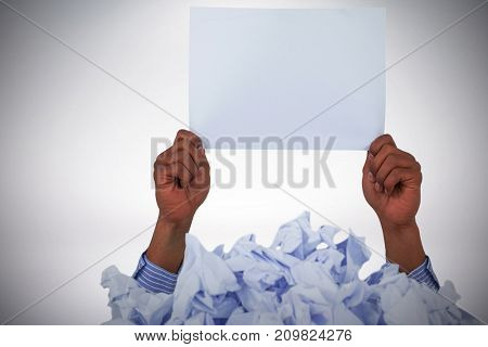 Heap of crumpled paper with hand holding blank page against grey background