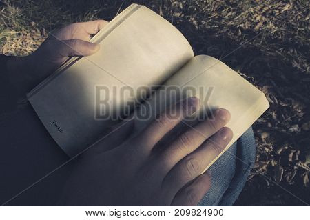 The guy is reading a book that says