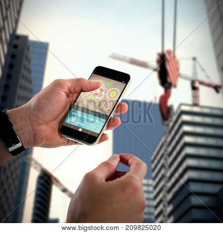Close-up of man holding 3D mobile phone against composite image of studio shoot of a crane
