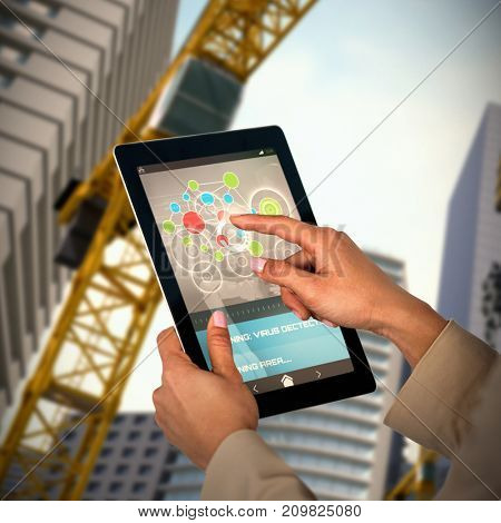 Businesswoman using digital tablet against 3d image of buildings and cranes