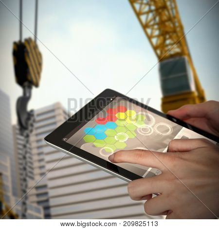 Close-up of businesswoman holding digital tablet against 3d image of cranes by buildings