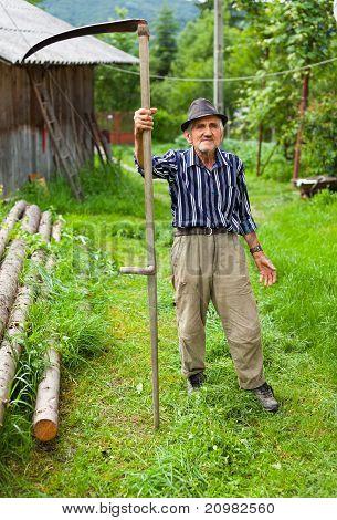 Old Rural Man Using Scythe