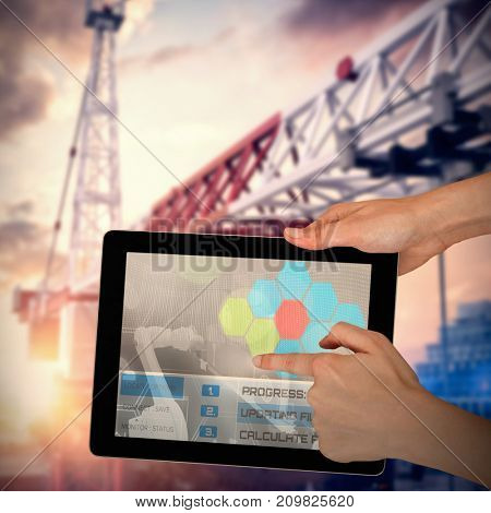 Hands touching digital tablet against white background against 3d image of crane in city during sunset