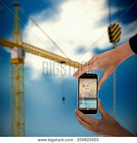 Cropped hands of businesswoman holding mobile phone against 3d image of yellow crane