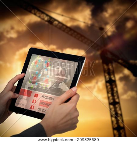 Cropped image of businesswoman holding digital tablet against 3d image of crane against cloudy sky