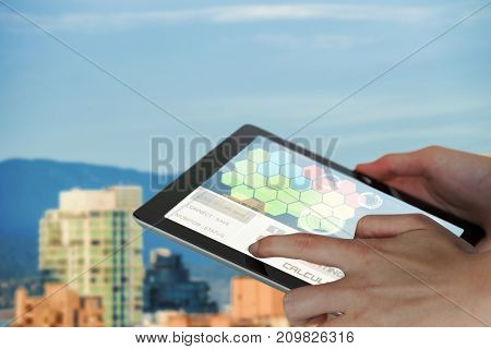 Close-up of businesswoman holding digital 3D tablet against buildings in city against blue sky