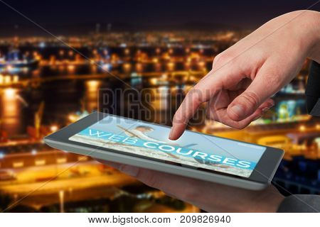 Businesswoman hand using digital 3D tablet against illuminated harbor against cityscape