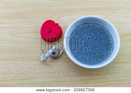 Sweet basil in white cup and red measuring tape shape heart on wooden background.Indicate for slim and good health.