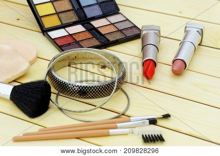 Cosmetic set including lipstick,eye shadow,sponge,brushes and bracelets on wooden background.