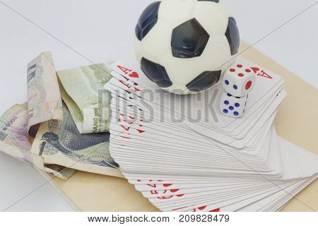 Concept of betting and gambling with game cards,money and toy soccer ball.
