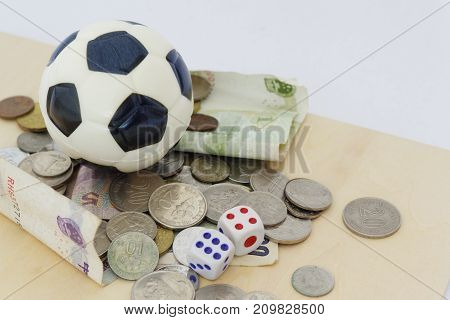 Mini soccer ball on top of playing cards with dices and money in different currency. Concept of betting and gambling.