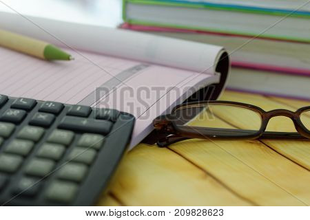 Calculator,spectacles,pen,receipt and invoice book and stack of books in the background.