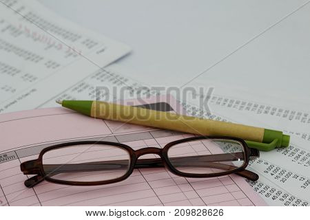 Pen, eye glasses, Invoice and bill book. Business concept
