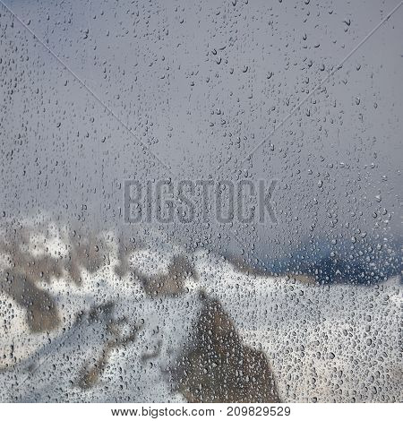 Rain drops on window glasses surface with mountain background . Natural Pattern of raindrops isolated on mountain background.