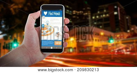 Cropped hand holding 3D mobile phone against illuminated roads by building in city