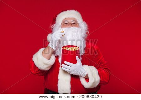 Santa Claus watching TV, eating popcorn. Christmas. Red background. emotions fear surprise
