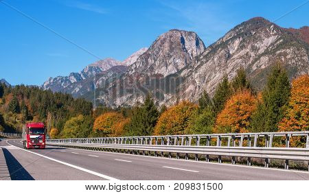 TYROL AUSTRIA - October 14 2017: Red truck on a high-speed mountain road. In the background are mountains and trees with red and yellow leaves.