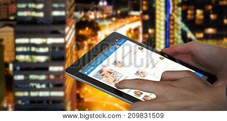 Close-up of businesswoman holding digital 3D tablet against glowing road amidst building in city at night