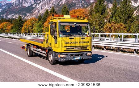 TYROL AUSTRIA - October 14 2017: Car tow truck in a hurry to help. In the background are mountains and trees with red and yellow leaves.