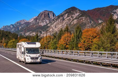 TYROL AUSTRIA - October 14 2017: Camper on a high-speed mountain road. In the background there are mountains and trees with red and yellow leaves.