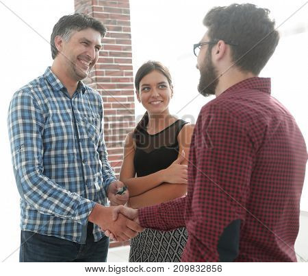 Happy young business people shaking hand at creative office