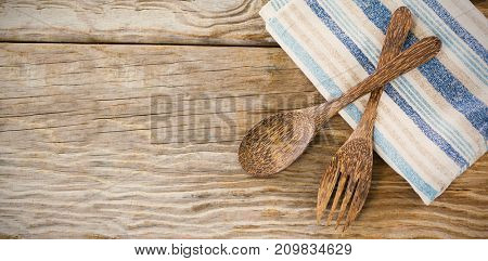 Overhead view of wooden spoon and fork with napkin on table