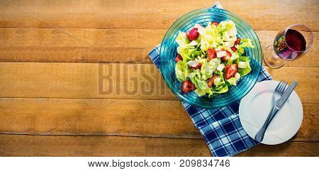 Overhead view of fresh salad in bowl with red wine on wooden table