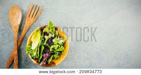 Overhead view of fresh salad in bowl by wooden spoon and fork on table